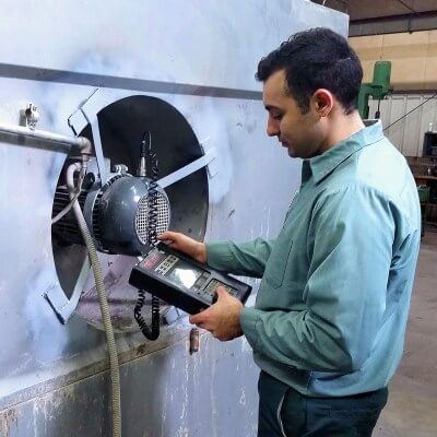 Technician performing vibration services on industrial fan